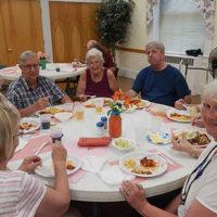 Friends enjoy the weekly community dinner at Trinity Church. Photo/Melanie Petrucci