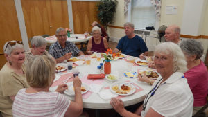 Friends enjoy the weekly community dinner at Trinity Church. Photo/Melanie Petrucci