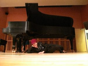 Cynthia Lee Wong relaxes under the grand piano after a concert in New York in 2008. (Photo/George J. Kunze)