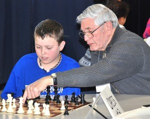 Fifth-grader Brenden Morris learns chess moves from volunteer John Richards during the recent session of Board Games Buddies.