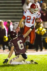 St. John's Zach Pedone tries to leap over Algonquin's Burke Dion to avoid a tackle while returning a punt.
