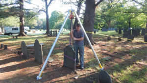 Mike Gallagher of Westmill Preservation Services works to remove a grave marker. Photo/Melanie Petrucci