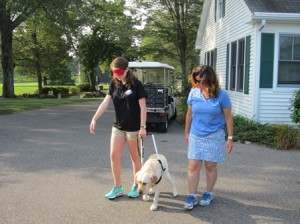 With the help of GDA Canine Development Assistant Yvette Sheehan ( r ) Julia Gittlen experiences what it is a like for a person with limited vision to walk with guide dog Alani.