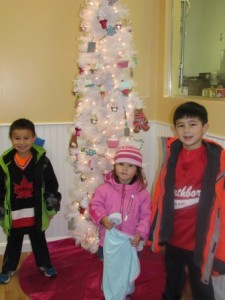 (l to r) Ethan, Hayden and Calvin Chan check out the decorated tree at the CocoBeni Confections stop, where kids were able to decorate their own cupcakes.