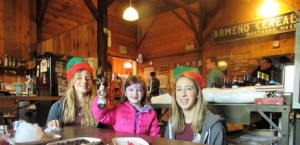 Riley Coombs (middle), with Marley (left) and Raye Parks, shows off her coffee bean ornament made at the Armeno Coffee Roaster's trolley stop.