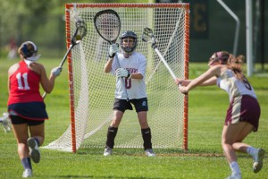 Algonquin goalie Bella Rino defends the goal as North Middlesex' Madison Ozog (#11) prepares to shoot.