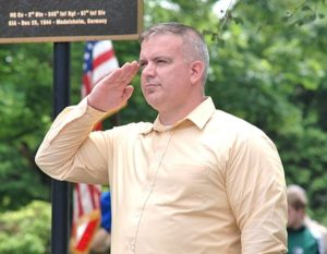"Adam Costello, director of Central Massachusetts Veterans' District, salutes as ""Taps"" is played."