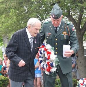 World War II veteran Harvey Chapdelaine is assisted by Parade Leader Bruce Goldsmith as he lays a wreath at the World War II – Korean War – Vietnam War Memorial.