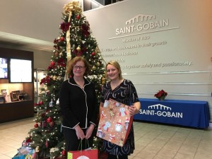 Anne Hardy (left), site director of Saint-Gobain's Northborough R & D Center, and Lauren Petit, manager of communications and community relations for Saint-Gobain Abrasives, Inc., show off gifts donated by employees. (Photo/Lori Berkey)