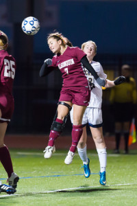 Algonquin's Kendall Sweeney (#7) leaps as she heads the ball in the state championship game against Needham.