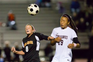 Marlborough's Abby Chrisafedeis (#8) and Algonquin's Zoe Chang (#19) prepare to head the ball