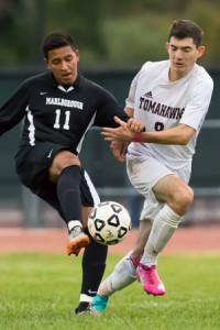 Marlborough's Kevin Herrera (#11) holds off Algonquin's Alex Sena-Leo (#9) as he kicks the ball