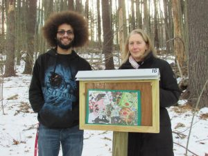 Zach Youssef and MaryEllen Remillard stand at one of the StoryWalk kiosks at Assabet Park Trail. (Photo/submitted)