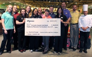 Jean McMurray, seventh from left, accepts a check from the Northborough Wegmans store team that orchestrated a recent