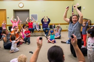 Alexandra Andrews, a music teacher from Apple County Music Together, leads a group of children and parents in a song.