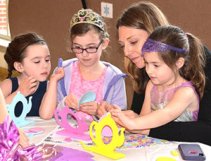 Beth Rutman helps create teapot-shaped photo frames with her daughters (l to r) Greta, 4; Amelia, 7; and Reagan, 4. Photos/Ed Karvoski Jr.