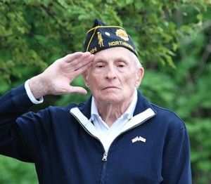 Armand Charest, Army veteran of the Korean War, salutes as the American flag is risen.