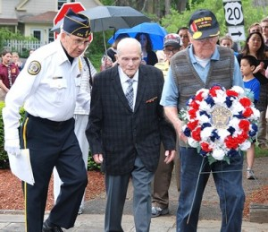 Parade Chair Gerard Bourque assists World War II veterans Harvey Chapdelaine and Connie Ludovico as they lay a wreath at the World War II – Korean War – Vietnam War Memorial.