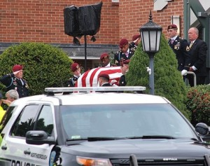 Pallbearers carry the flag-draped casket from the church.
