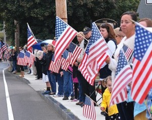Residents pay their respect with American flags.