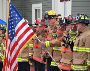 Firefighters salute as the procession passes the station.