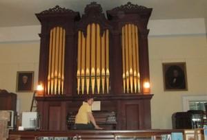 Llanda Richardson sits in front of the newly restored organ at the Northborough Historical Society Photo/Alexandra Molnar