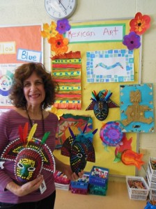 Marcia Waldman, Peaslee School art teacher, stands in front of a sample board of projects that will be displayed in the school's upcoming opening night for The Art of Mexico. (Photo/submitted)