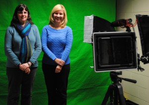 Amy Brewis, instructional technology specialist, and fourth-grade teacher Karyn Fisher stand in front of the green screen in the school's new recording studio. (Photo/Nance Ebert)