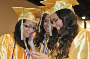 Glenda Maldonado, Claritza Taylor, and Paloma Oliveira, all from Clinton, share a laugh while waiting to line up for graduation.
