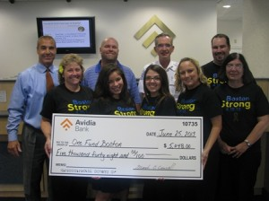 Presenting the check to the One Fund Boston are: (front row l-r) tellers Donna Gravelle, Molly Kelly, and Monica Serra; Head Teller Katy Cuddahy-Kirouac; and Portfolio Manager Mary Laitila; (back row l-r) Thomas Allain, senior vice president and senior commercial relationship officer of Avidia Bank; Brian Whitney, president of Bay State Apparel; Jim Hooley, chief of department, Boston EMS; and Todd Wood, Avidia Bank branch manager. (Photo/submitted)