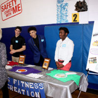 At the club's 75th anniversary celebration, (l to r) Tyler Lechman, Daisjaugn Jermaine Bass, and Sincere Redd, staff members at the Boys & Girls Clubs of MetroWest, speak with guests about the Sports, Fitness & Recreation programs