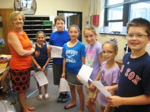 (l-r) Shrewsbury's Spring Street School secretary Judith Adair gathers with fourth grade students (l to r)  Emma De Pina, Ben Barter, Maeve Gale, Carrie Hess, Alina Shkurikhina and Patrick Hastings, as the students make the morning announcements over the PA system at school.  Photo/Mary Pritchard