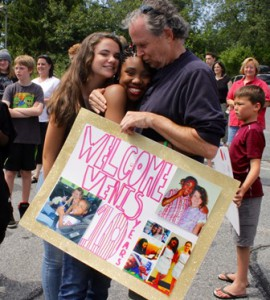 Jonanthan Golding, (r), and daughter Elizabeth, (l), hug and kiss Venis, welcoming her back home. The sign is filled with photo memories over the past ten years.