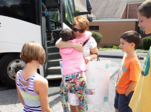 London, 8, runs off the bus to hug all members of her host family. This is her second summer with this family.