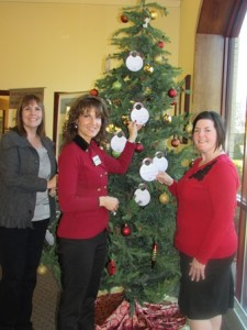 Northborough Senior Center Director Kelly Burke, Home Instead Marketing Director Wendy Nollman, and Northborough Central One Branch Manager Kate Shaw decorate a Christmas tree in Central One's lobby with gift request tags to benefit Northborough senior citizens. Photo/submitted