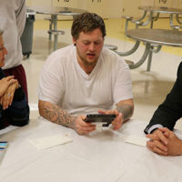 Berlin's Director General of Prison and Probation Administration and Department of Criminal Law Susanne Gerlach (left) and Middlesex Sheriff Peter J. Koutoujian (right) speak with a P.A.C.T. participant regarding educational tablets in use in the unit.
