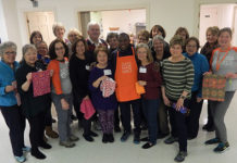 Patrick Ssenyonjo (center front in apron) surrounded by Days for Girls Chapter members Photo/Melanie Petrucci