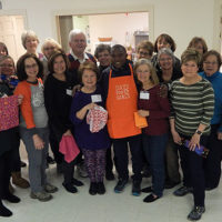 Patrick Ssenyonjo (center front in apron) surrounded by Days for Girls Chapter members. Photo/Melanie Petrucci