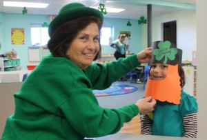 Kindergarten teacher Jane Curtin helps Lucy Rainey of Grafton with her leprechaun hat at Country Montessori Preschool and Kindergarten. The kindergarten class learned about the culture of Ireland during a weeklong study. Photo/submitted