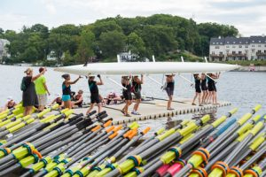 The Upper Valley (Hanover, N.H.) Women's Eight team works to place their shell in the water.