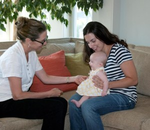 An experienced mom offers support to a new mom as part of the Visiting Moms program. (Photo/submitted)