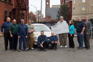 Members of the All Car Care team (in long-sleeved blue shirts) stand next to the car they helped restore with (l to r) Chuck Lundberg, Clean & Green Car Wash and Detail Center, Howard Priest, Ed Cunningham, Denise Sullivan, Michael Aspesi of Ted's of Fayville, Inc., and Carl Bruso Jr. of Framingham Ford Lincoln. Photo/Valerie Franchi