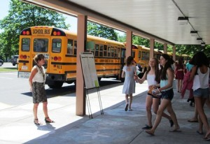 Students at the Robert E. Melican Middle School in Northborough head to the buses with report cards in hand on the last day of school, June 23, as teachers and staff wish them well for the summer. Photo/Alexandra Molnar