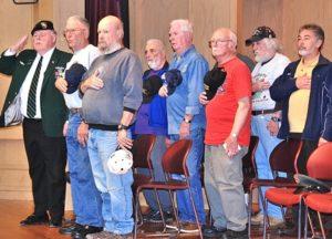 Vietnam War veterans stand as the national anthem is sung.