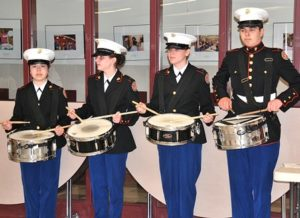 Marine Corps JROTC cadets play drums as the Vietnam veterans enter the cafeteria.