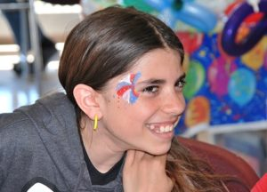 Faith Tompkins, 11, is pleased with the fireworks design painted on her face.