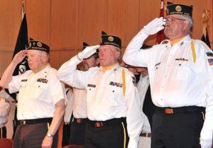 Vietnam War veterans salute as the national anthem is sung.