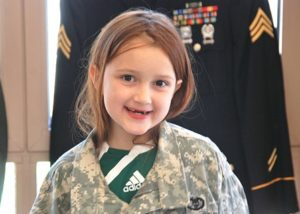 Hailey Costello, 9, tries on an Army fatigue jacket.