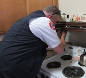 Lt. Chris Dano installs a firestop over a resident's stove at the Colonial Gardens complex.