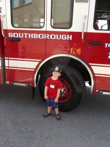 Tyler, age 4, poses with his fire helmet in front of a Southborough fire truck.